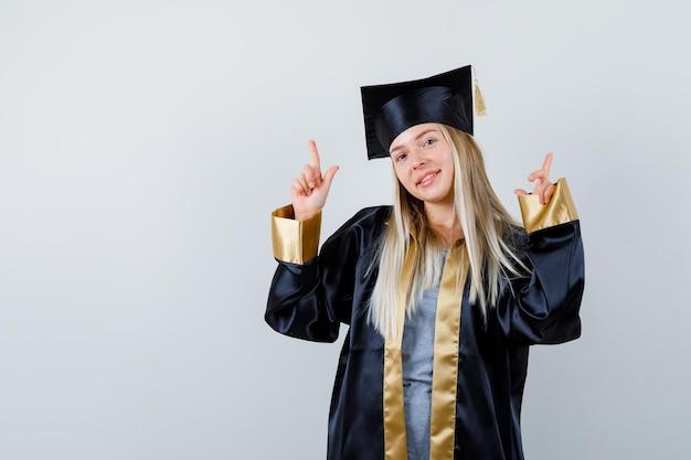 Ragazza bionda in abito da laurea e berretto che punta con l'indice e sembra carina