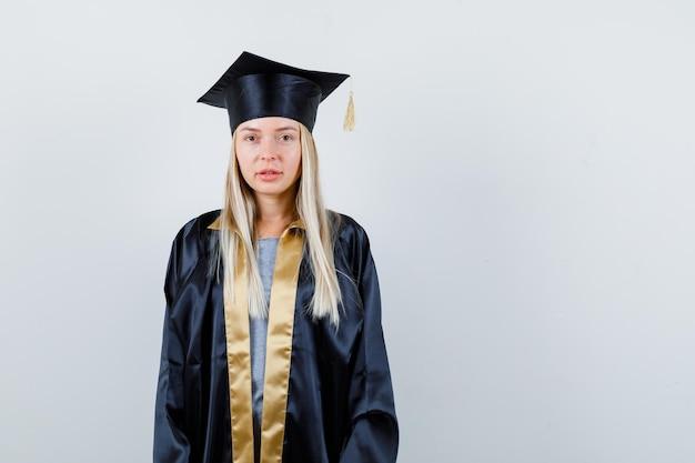 Ragazza bionda in abito da laurea e berretto in piedi dritta e in posa davanti alla telecamera e sembra seria Foto Gratuite