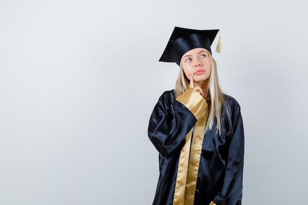 Ragazza bionda in abito da laurea e berretto in piedi in posa di pensiero e guardando pensierosa