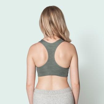 Ragazza bionda in reggiseno sportivo grigio per servizio fotografico activewear