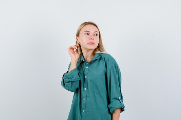 Blonde girl in green blouse looking away while posing at camera and looking enchanting