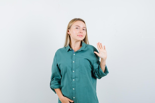 Ragazza bionda in camicetta verde che mostra il segnale di stop mentre tiene la mano sulla pancia e sembra carina