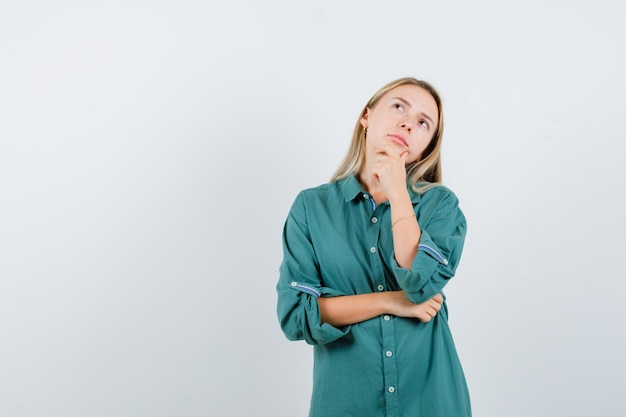 Ragazza bionda in camicetta verde in piedi in posa di pensiero e guardando pensierosa