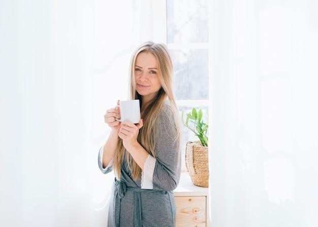 Blonde girl having coffee in the morning