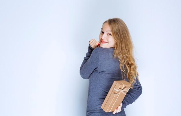 Ragazza bionda che nasconde una confezione regalo di cartone dietro di sé.