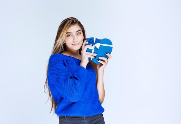 Белокурая девушка держит голубую подарочную коробку в форме сердца.