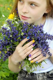夏に牧草地の野花の花束を持っているブロンドの女の子。子供の美しいマニキュア。
