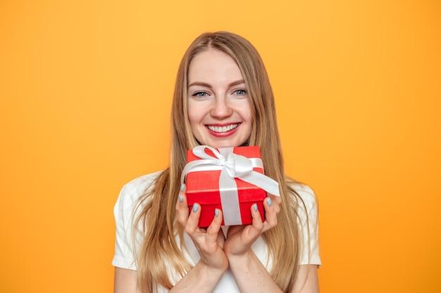 Блондинка девушка держит подарочную коробку, изолированные на желтом фоне в студии