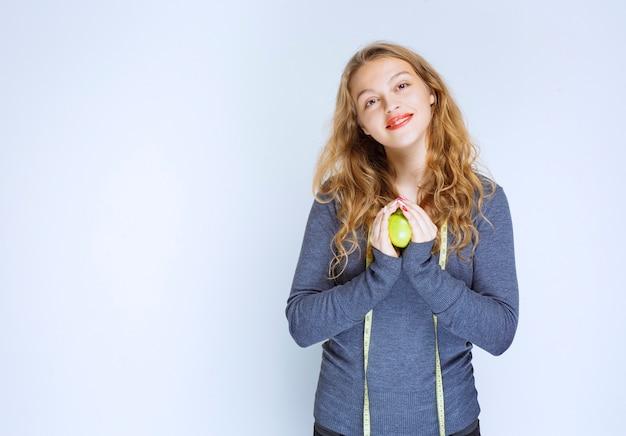 Блондинка держит в ладонях зеленое яблоко.