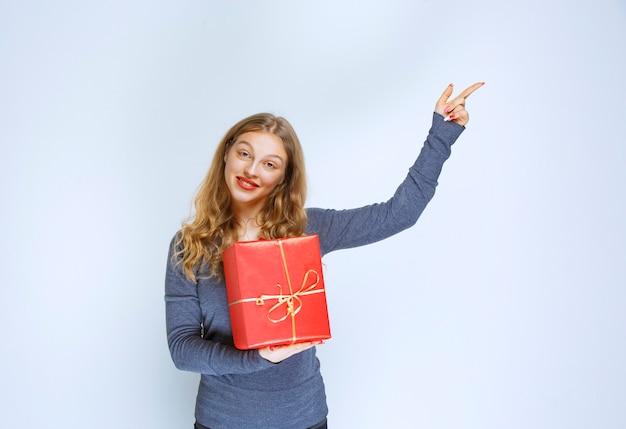 赤いギフトボックスを持って誰かを見せているブロンドの女の子。