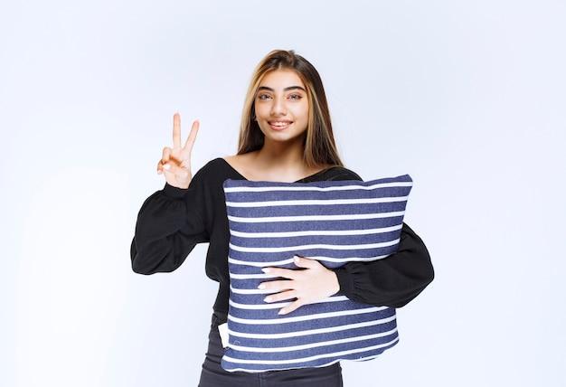 縞模様の青い枕を保持し、満足感を感じているブロンドの女の子。