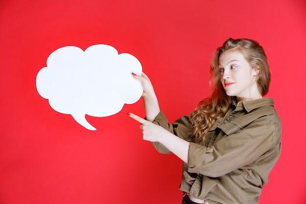 흰 구름 모양 빈 ideaboard를 들고 금발 소녀.