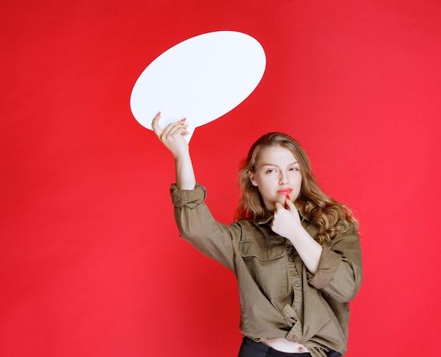白い卵形のthinkboardを保持し、前向きに感じているブロンドの女の子。