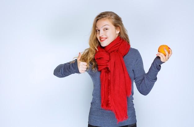 Блондинка держит апельсиновый плод и наслаждается вкусом.