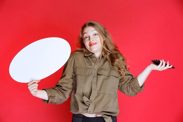 한 손에는 ovale ideaboard를 다른 손에는 스마트 폰을 들고 금발 소녀.