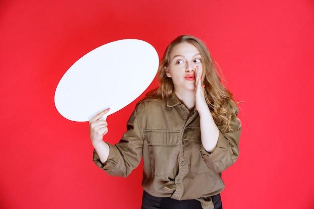 卵形のthinkboardを保持し、沈黙を求めているブロンドの女の子。