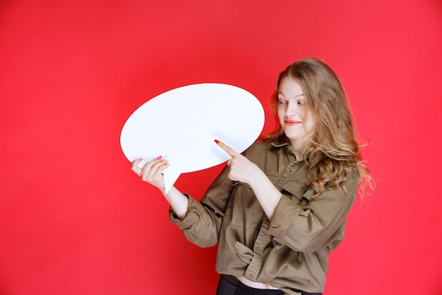 Ovale thinkboard를 잡고 그것을 가리키는 금발 소녀.