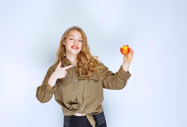 Белокурая девочка держит и продвигает красный персик.