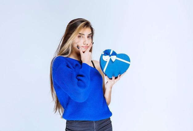 Ragazza bionda che tiene una scatola regalo blu a forma di cuore e pensa.