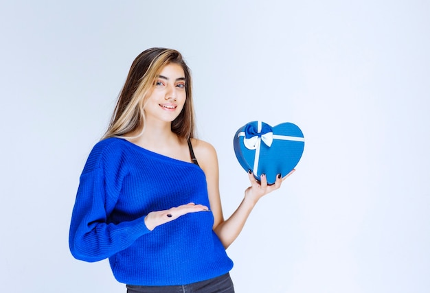 Ragazza bionda che tiene una confezione regalo blu a forma di cuore.