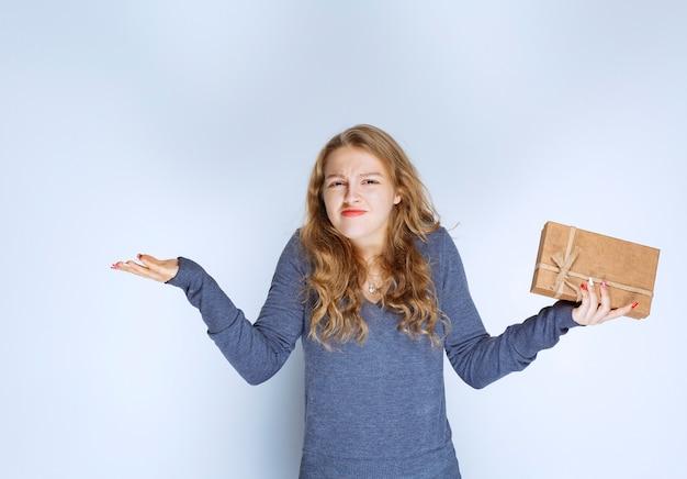 Ragazza bionda che tiene in mano una scatola regalo di cartone e sembra confusa e premurosa.