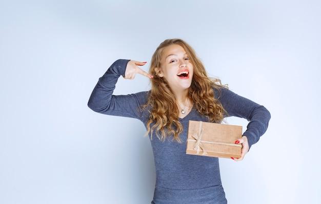 Ragazza bionda che tiene in mano una confezione regalo di cartone e la indica.