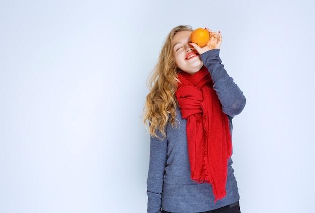 Blonde girl holding and demonstrating orange fruits.