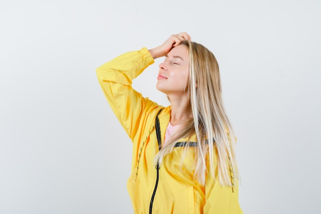 Blonde girl holding hand on head in yellow jacket and looking peaceful.