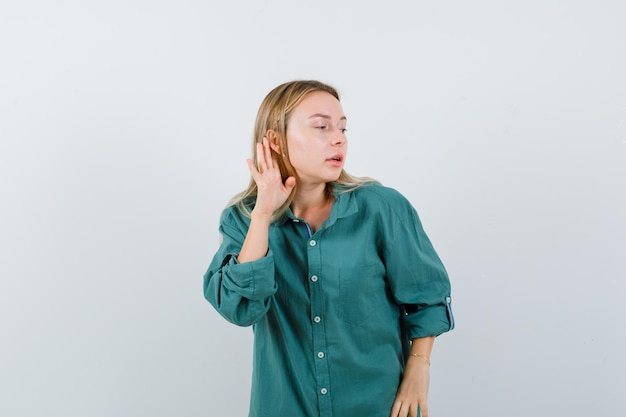 Blonde girl holding hand near ear to hear something in green blouse and looking focused
