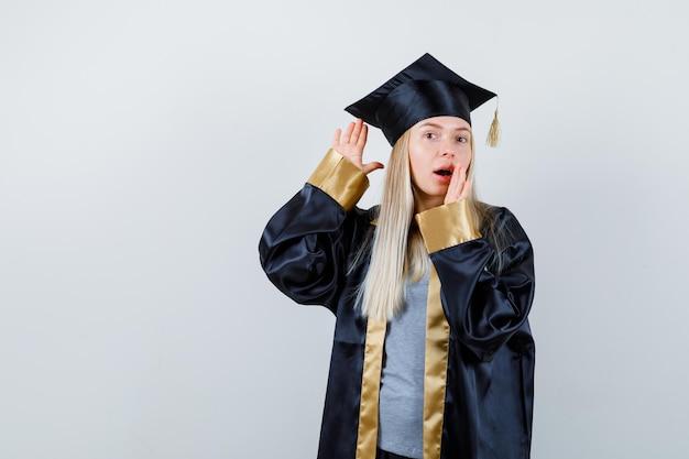 Ragazza bionda che tiene la mano vicino all'orecchio per sentire qualcosa, tenendo la mano vicino alla bocca in abito da laurea