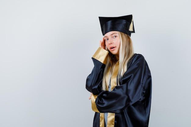 Блондинка держит руку на локте, прислонившись щекой к ладони, глядя через плечо в выпускном платье