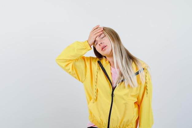 黄色のジャケットで額に手をつないで物思いにふけるブロンドの女の子