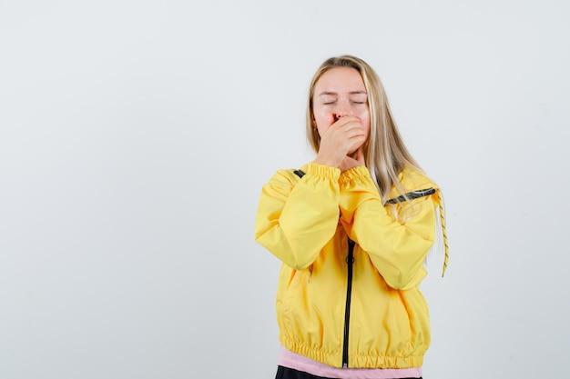 노란색 재킷에 입에 손을 잡고 졸린 찾고 금발 소녀.