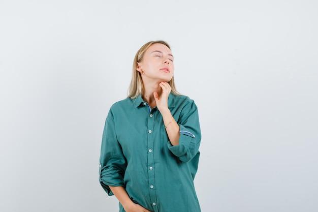 Блондинка держит руку на шее, закрывает глаза в зеленой блузке и выглядит спокойно