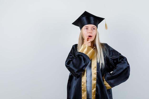 卒業式のガウンとキャップで口の近くに指を置き、自信を持って見ながら腰に手をつないでいるブロンドの女の子