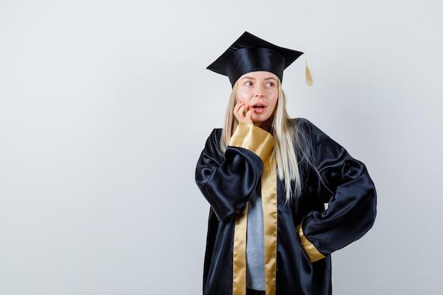 卒業式のガウンとキャップで口の近くに手を置き、自信を持って見ながら腰に手を握って