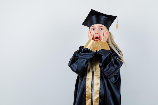 Blonde girl holding hands on cheeks in graduation gown and cap and looking surprised