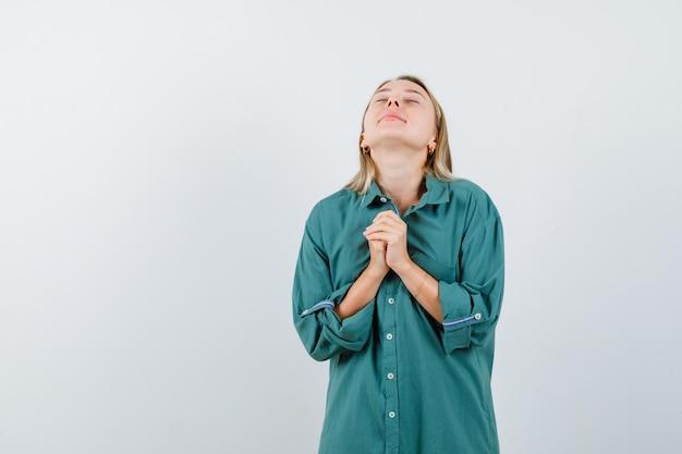 Ragazza bionda che si tiene per mano stretta, pregando in camicetta verde e guardando concentrata