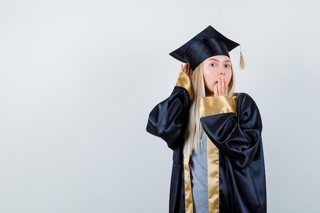 Blonde girl holding hands near ear to hear, covering mouth with hand in graduation gown and cap and looking surprised.