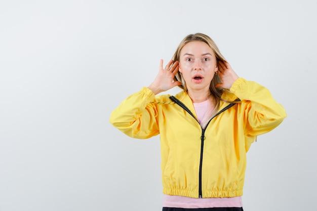 Ragazza bionda che si tiene per mano vicino all'orecchio per sentire qualcosa in maglietta rosa e giacca gialla e sembra sorpresa.