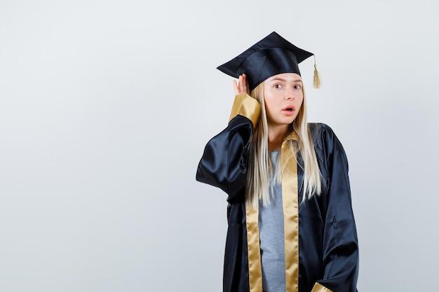卒業式のガウンとキャップで聞くために耳の近くで手を握って、驚いて見えるブロンドの女の子。