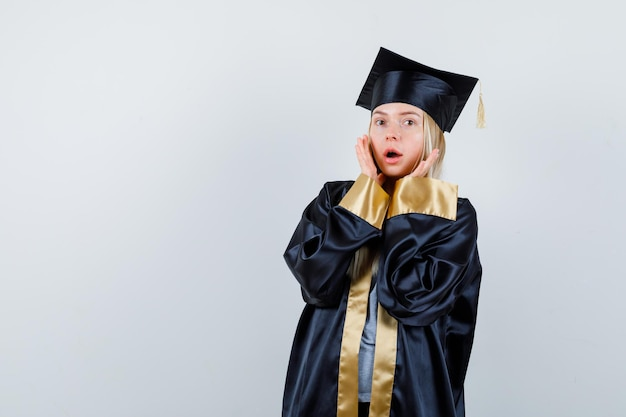 Blonde girl holding hands near face, opening mouth in graduation gown and cap and looking surprised