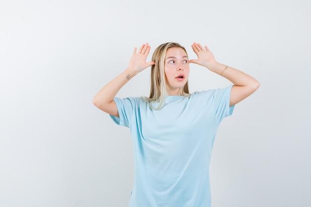 Ragazza bionda che tiene le mani vicino alla testa, distogliendo lo sguardo in maglietta blu e guardando carino. vista frontale.