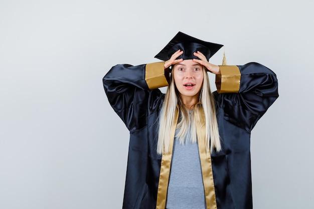 卒業式のガウンとキャップで頭に手をつないで、驚いて見えるブロンドの女の子。