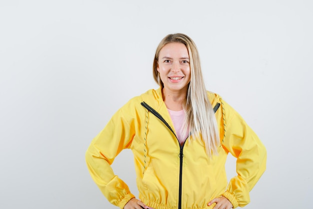 黄色のジャケットで腰に手をつないで、陽気に見えるブロンドの女の子。
