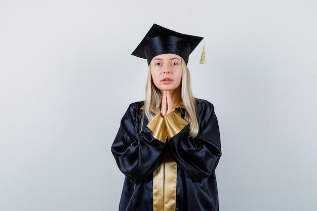 Ragazza bionda che si tiene per mano in posizione di preghiera in abito e berretto da laurea e sembra seria