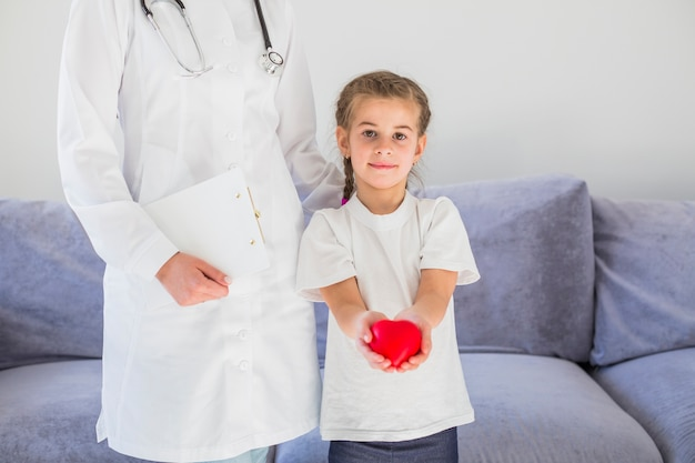 Blonde girl holding heart with doctor