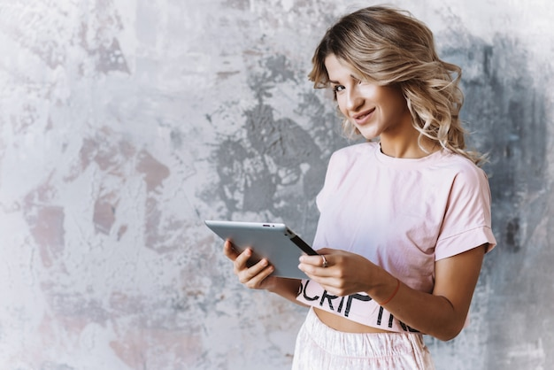 Blonde girl holding an ipad in her hands