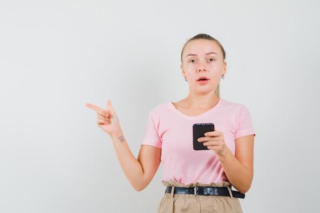 Блондинка девушка держит мобильный телефон, указывая в сторону в футболке, вид спереди брюки.