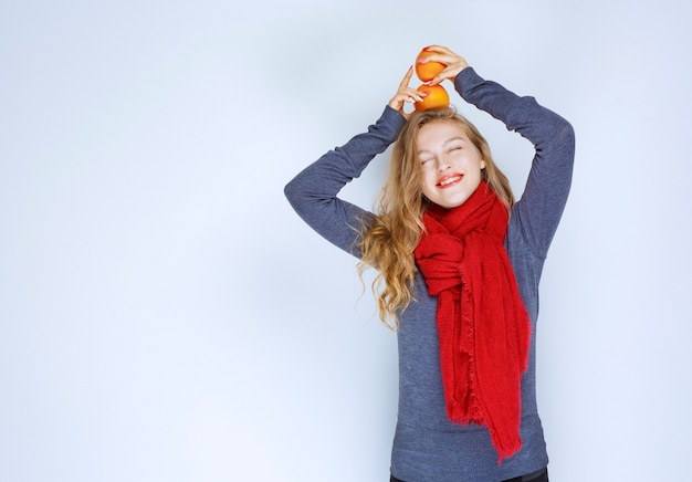 Blonde girl holding orange fruits over her head.